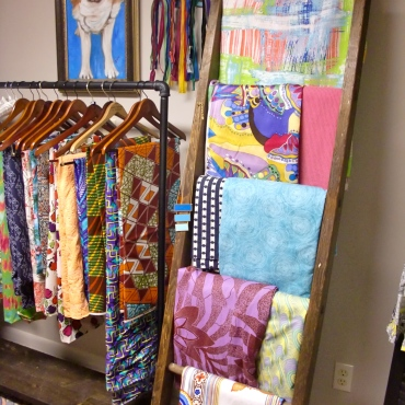 Fabric stash hanging on an old ladder and clothing rack.